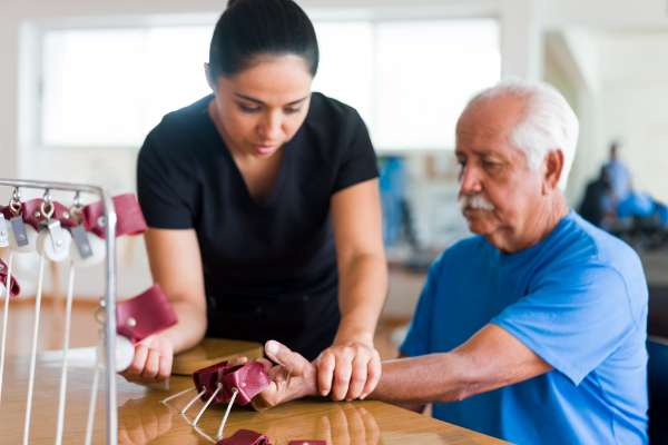 A senior male patient sitting and exercising his hand with a physical therapy device next to a occupational therapist.