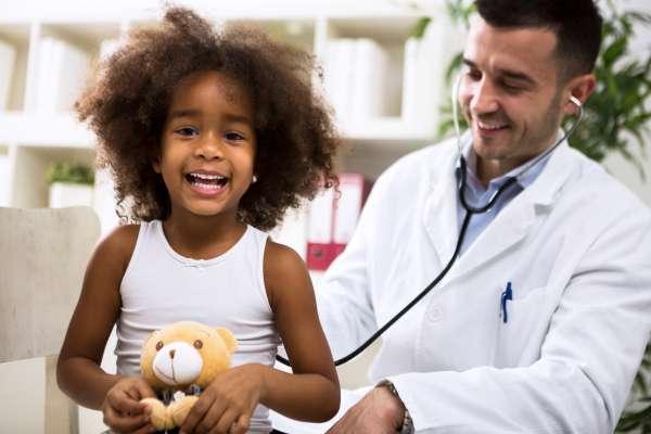 Pediatrician doctor examining happy smiling kid at hospital